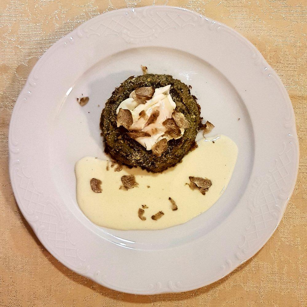 Savarin di carciofi con uovo in camicia, salsa di formaggio e tartufo bianco d'Alba